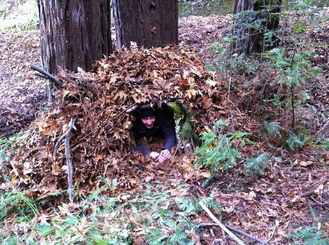 Survival course student tries out a brush shelter.