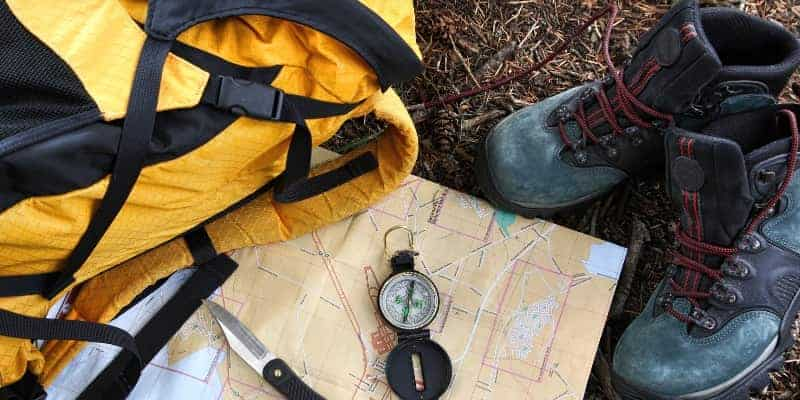 backpack map compass and hiking boots for bugging out
