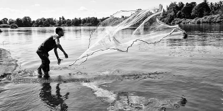 Fishing with net from side of river