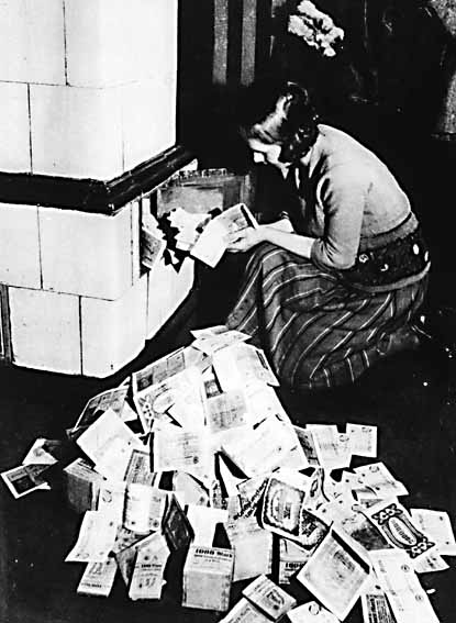 Image of a woman lighting a fire with bank notes (Weimar Republic, 1922)