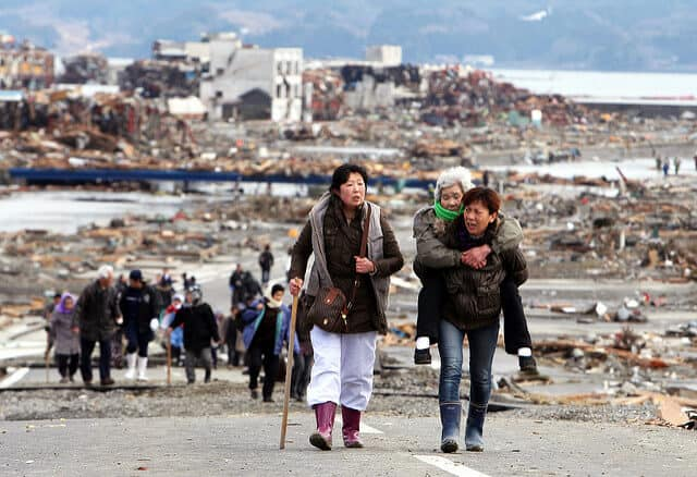 elderly woman being carried out of earthquake zone