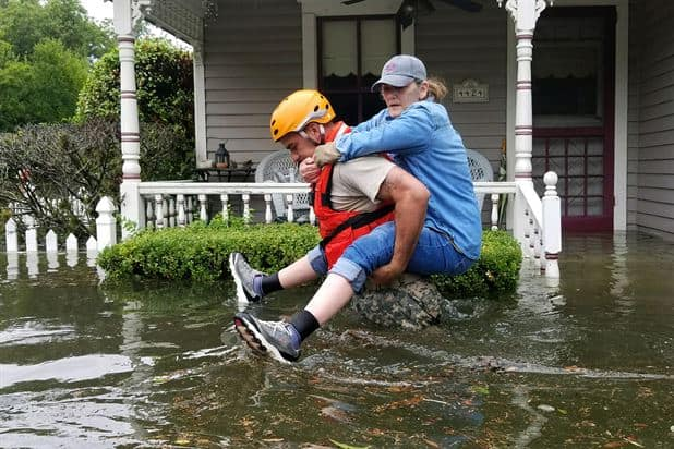 woman being evacuated during flood