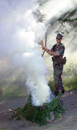 Soldier practices making a smoke signal