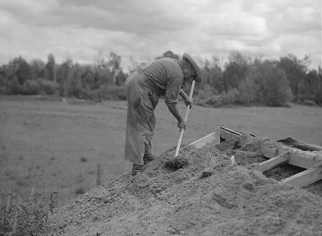 old photo of man burying the top of root cellar