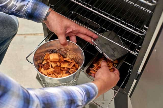 putting woods chips into a smoker